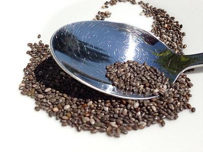 silver metal spoon with black grains