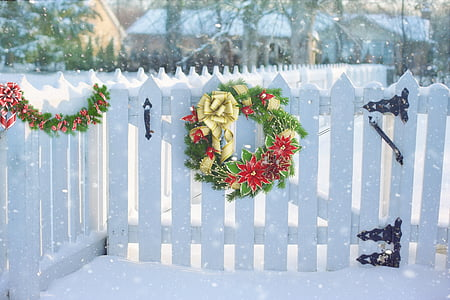 green and red Christmas wreath on white wooden fence