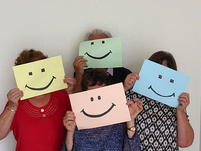 group of people holding smiley illustrations