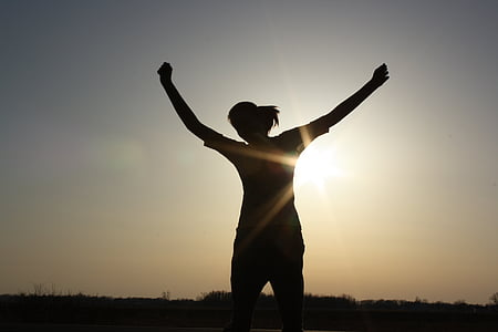 silhouette of woman raising her hands during sunset