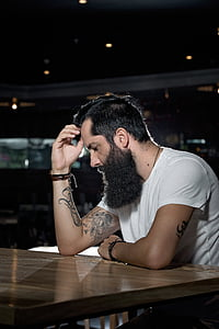 man in white crew-neck t-shirt thinking while leaning on brown wooden table