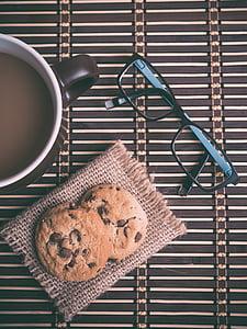 two round cookies beside black framed eyeglasses and black ceramic mug with liquid
