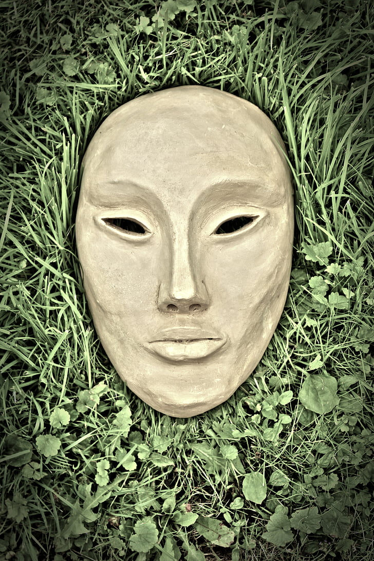 brown concrete mask on green grass
