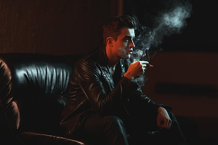 man holding cigarette stick while sitting on chair