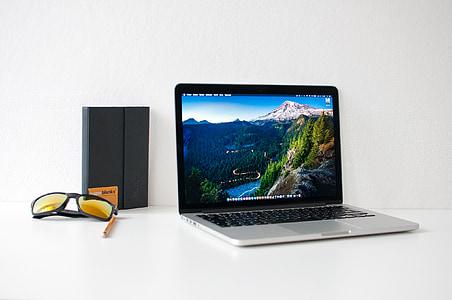 MacBook Pro beside black framed sunglasses