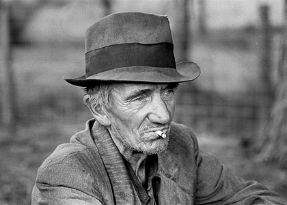 grayscale photo of man with hat and cigarette