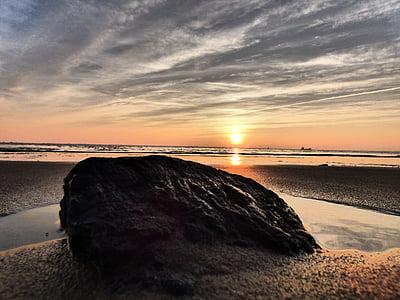 rock on beach shore during golden hour