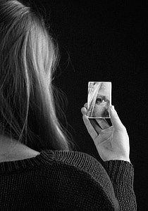 grayscale photography of woman holding piece of mirror
