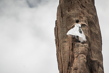 low angle photography of bride climbing rock formation