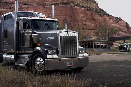 grey semi truck near brown mountain during daytime