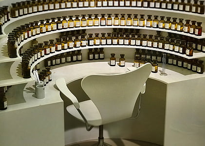 chair surrounded by bottles on table