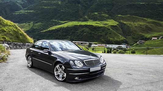 black Mercedes-Benz sedan parking on road near mountain at daytime