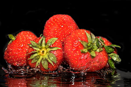 strawberries splashing on water