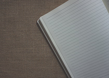 white notebook on brown surfac