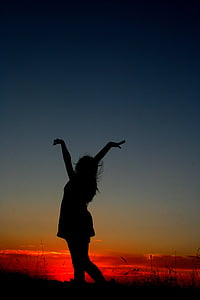 photography of woman raising her hands during sunset