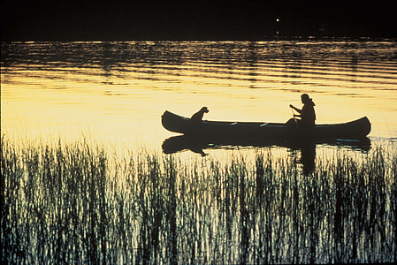 silhouette of woman and dog in canoe on body of water