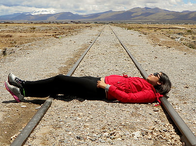 woman laying on train rail