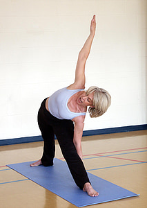 blonde haired woman wearing white tank top and black pants standing on blue yoga mat