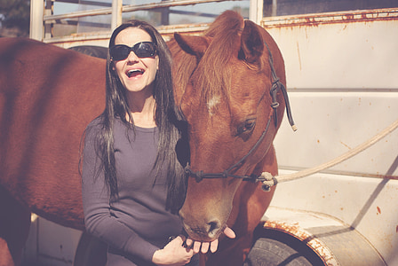 smiling woman standing beside brown horse