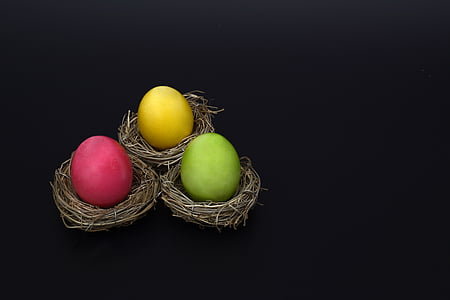 three yellow, green, and pink eggs