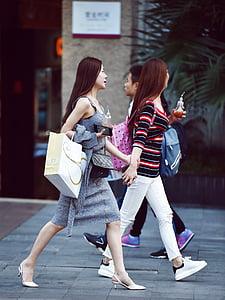 women walking beside man at daytime