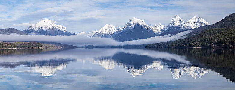 landscape photography of snow covered mountain range and body of water