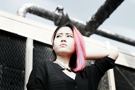 pink-haired woman wearing black shirt standing near white building