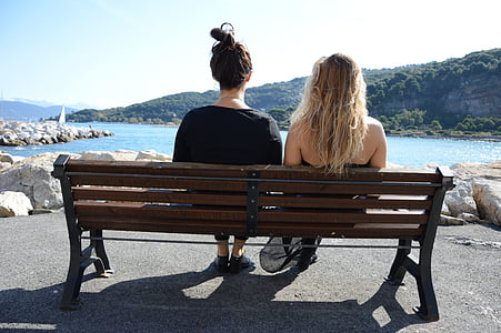 two women sitting on bench near body of water and mountains during daytime