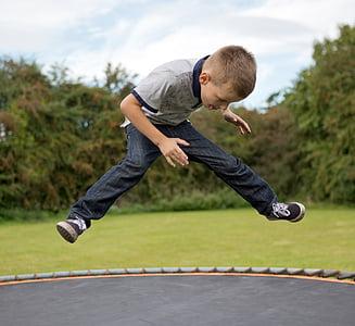 boy playing on trampoline during daytime