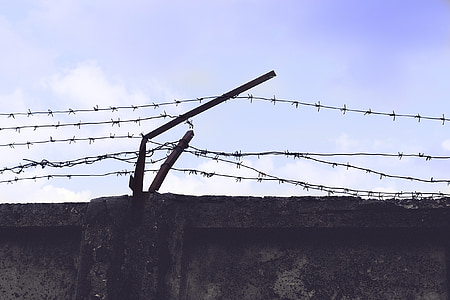 high angle photography of concrete wall with barbed wire