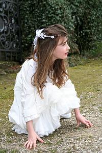 girl in white long-sleeved dress posing near green bushes