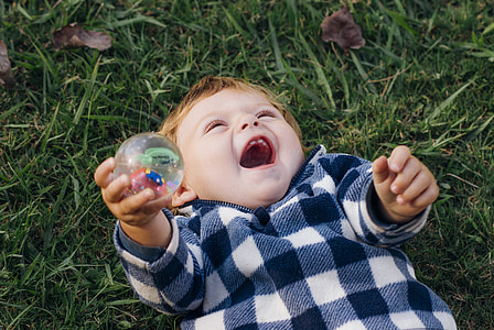 boy lying on green grass holding ball