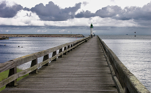 empty brown wooden dock bridge with lighthouse tower