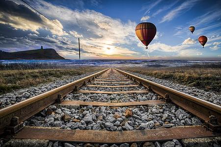 rusted trail rail near three hot air balloons during daytime