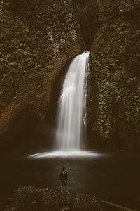 man in black jacket standing near waterfalls