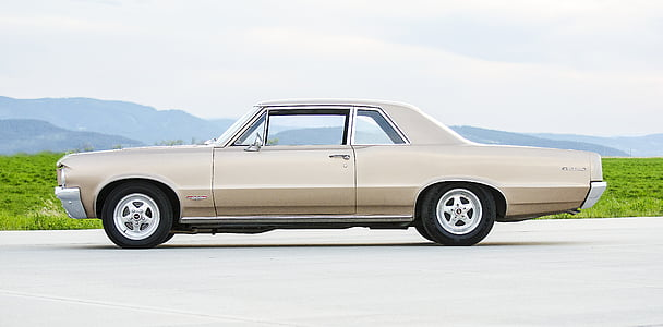 classic beige coupe parked on concrete pavement