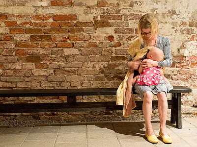 woman carrying baby and sitting on bench