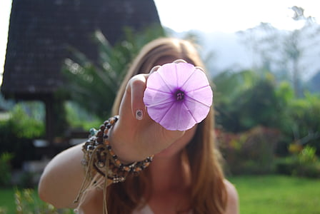 woman holding purple petaled flower