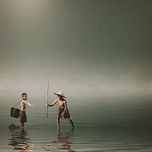 two boys catching fish on beach