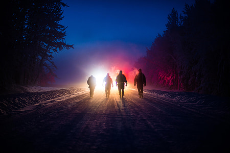 silhouette of 4 persons walking in road