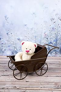 white bear plush toy on brown steel stroller