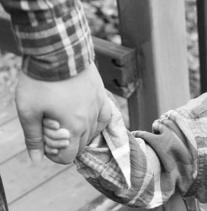 grayscale photo of two person holding hands