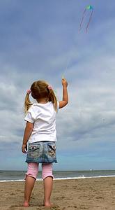 girl holding string of kite flying under white cloudy sky near seashore at daytime