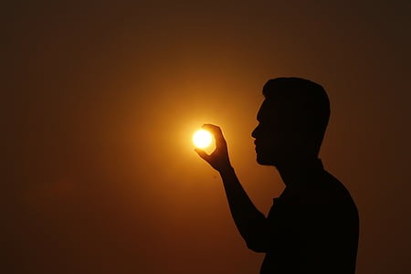 forced perspective photo of silhouette of man holding sun