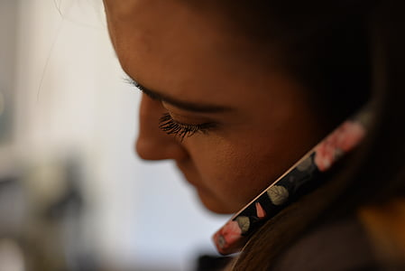 selective focus photography of woman putting phone on her left ear