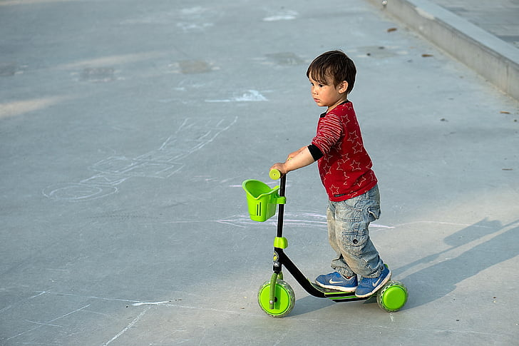 boy riding black and green 3-wheeled kick scooter
