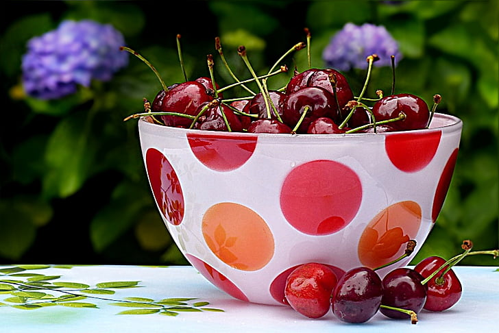 cherries in round white and red polka-dot glass bowl