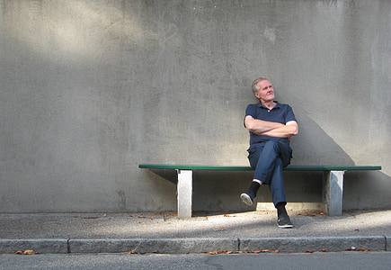 man in polo shirt sitting on bench