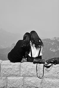 grayscale photo of two women sitting on cinder block wall