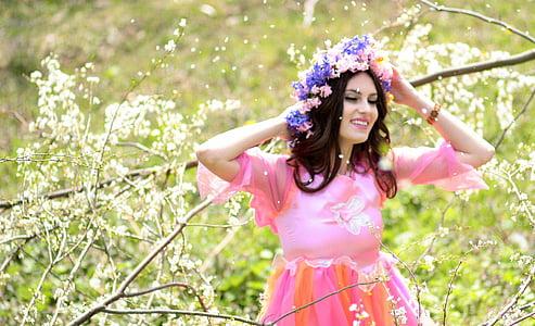 woman wearing pink dress and flower headdress beside tree branch